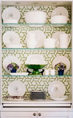 What FAB wallpaper.  Would be neat to open doors of armoire in my Dining Room and paper the back of it and install glass shelves to display my green & white wedding china. Love!