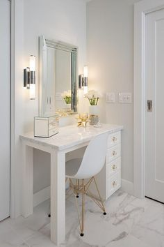 White master bathroom is completed with an Eames Molded Plastic Chair placed on marble porcelain floor tiles in front of a white dressing table accented with brass and glass hardware and marble porcelain countertop. Dressing Room Decor, Dressing Table Design, Makeup Dressing Table, White Dressing Tables, Dressing Table Lights, Vanity Room, Vanity Set, Mirror Vanity, Vanity Ideas