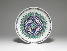 Dish. Central cruciform design of palmettes.Cavetto bears lobed lappets,darts,inner rim lappet band of half prunus blossoms. Made of black, turquoise, cobalt, red (bole) painted and glazed (crazed) and drilled ceramic, pottery.
