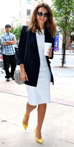 Jessica Alba in a white crochet Victoria Beckham dress that she expertly styled with a long navy Atea Oceanie blazer, a studded Christian Louboutin cross-body purse, and bright yellow pumps.