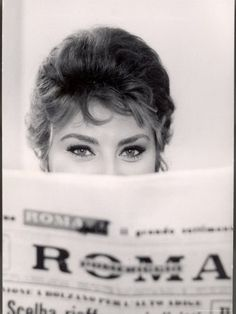 Actress Sophia Loren peeking over the top of Roma newspaper, 1950s