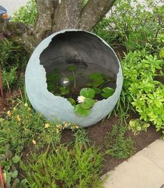 Little and Lewis water feature in Marie's Garden entry--- This is amazing.This is one AWESOME concrete sphere used as a water garden.Spray the inside of your concrete sphere with Rust-Oleum LeakSeal and fill with water for a pretty water feature.