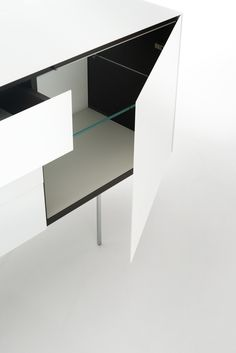 MAGIC BOX design Piero Lissoni | Series of storage furniture in tempered glass, glossy or opaque lacquered, glued 45°. The interior is in laminated opaque charcoal coloured wood and shelves in 10 mm. thick transparent extralight glass. Available with doors or with drawers, with or without thin legs in glossy chromed metal and in a wide range of dimensions. Push-pull opening system for the doors and the drawers. The models with doors, on demand, can be provided with cable outlets in the…