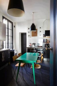 Black and white kitchen with teal table and hairpin leg chairs.