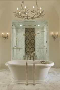 Oh wow! So gorgeous! Custom marble shower enclosure...two different shower fixtures a gorgeous accent panel, venting glass panels atop and what an elegant bath..marble flooring and creative custom lighting.