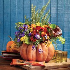 Blooming Pumpkin | To make this arrangement, choose your favorite pumpkin (we like the flat-bottomed Fairytale) and pick up some violas, pansies, red and green leaf lettuce, thyme, and rosemary to decorate.