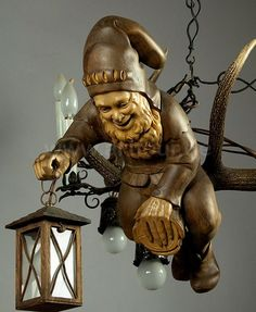 """Reminds of the """"Pirates of the Caribbean"""" ride at Disneyland and the pirate that hangs over the bridge with the lantern :-) Delightful Gnome Hanging Light executed by the woodcarver Jacob Christl, Passau - Germany. Antler Lights, Antler Chandelier, Black Forest Wood, Kobold, Gnome Garden, Wooden Art, Woodland Creatures, Wood Sculpture, Hand Carved"""