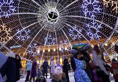 People stand inside a giant illuminated Christmas ball ornament at Octyabrskaya Square to mark Christmas and the upcoming New Year celebrations in Minsk, Belarus, December 29, 2015. EPA/TATYANA ZENKOVICH
