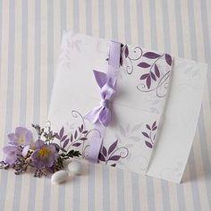Partecipazione composta da una parte esterna in carta trasparente, con decorazioni floreali ed interno in carta bianca, chiusa da un nastro in raso color lilla.
