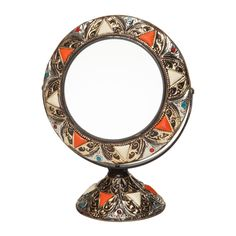 This free-standing vanity mirror brings a touch of exotic Morocco to your bedroom or bath. The swivel frame and stand consist of hand-formed and embossed brass-colored metal and henna-dyed bone inlays