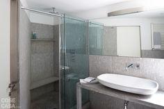 DOPO Il bagno è stato rinnovato con un rivestimento in lastre di beola bianca; l'ampia doccia in muratura con pareti scorrevoli in cristallo è in alternativa alla vasca.