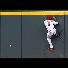 Cincinnati Reds center fielder Billy Hamilton (6) runs into the wall after leaping for a fly ball off the bat of St. Louis Cardinals left fielder Randal Grichuk (15), allowing a triple in the top of the third inning of the MLB game between the Cincinnati Reds and the St. Louis Cardinals at Great American Ballpark in downtown Cincinnati, on Tuesday, Aug. 4, 2015. The Enquirer/Sam Greene