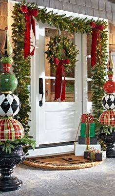 whimsy porch decor with evergreen garlands, lights, large ornament topiaries and gift boxes