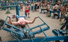 People train at the Kachalka outdoor gym on the banks of river Dniper in Kiev June 26, 2013. The impromptu gym, established in the 1970s and now containing around 200 makeshift training machines mostly made from scrap metal, has enjoyed popularity with inhabitants of the Ukrainian capital for more than 40 years. REUTERS/Gleb Garanich