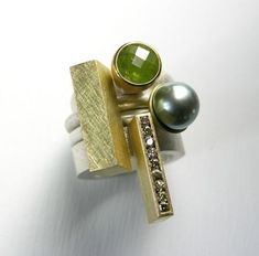 Katzie Hughes; Set of four rings in silver, 18 & 22ct gold, tourmaline, natural-green diamonds and tahitian pearl.