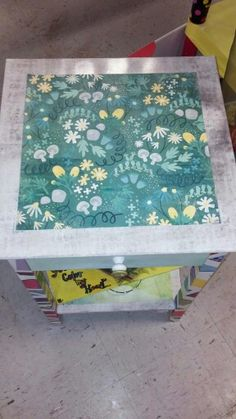 Top of and bottom shelf has scrapbook paper sealed on it