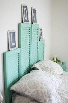 tete de lit alinea en bois bleu, murs blancs dans la chambre à coucher