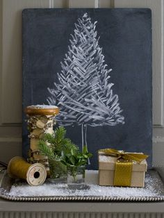 """Chalkboard Christmas Tree Add small cuts of greenery in glass candle holders for an inexpensive winter touch. """"Vignettes are a simple way to add holiday decor to your home,"""" says stationery designer Debra Norton of Vintage Paper Parade. Here, """"a roll of twine, a spool wrapped with beads, fresh greenery and an old slate add"""