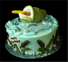 Fisherman's Birthday cake, Green and blue buttercream iced, round decorated with a large mouth bass, fishing lure, and cattails. Everything on this cake is EDIBLE. (Serves 8-80 party slices)