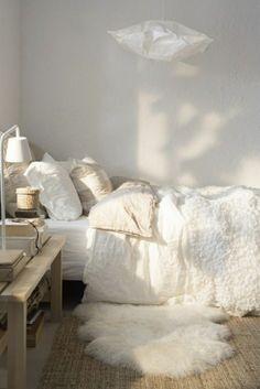 tapis fausse fourrure blanche, mur blanc, lustre en tissu blanc, chambre à coucher