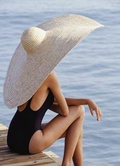 un grand chapeau de paille beige, femme au bord de la mer