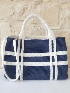 Handbag made of blue and white lanyard. On the body bag white strips are applied to form an original reason of weaves. The vertical stripes extend to form the two hand grips. The bag is fitted with a detachable shoulder strap has a lateral bellow closed from Central magnet, magnetic and cotton lining in contrasting colour. Galvanic nickel trim Interior zipper pocket Internal jacket pockets applied 23 cm dimension L 35 cm d 12 cm, handle drop 15 cm, strap length 80 cm. Crochet and finish…