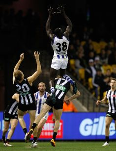 Majak Daw of the Kangaroos takes a spectacular mark over Jonathon Marsh of the Magpies during the 2016 AFL Round 18 match between the Collingwood Magpies and the North Melbourne Kangaroos at Etihad Stadium on July 2016 in Melbourne, Australia. Collingwood Football Club, Kangaroos, Melbourne Australia, Orlando, Take That, Wall, Sports, Hs Sports, Orlando Florida