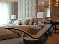 Para um ambiente confortável e clean, enxoval bege, móveis de madeira e cortinas claras.