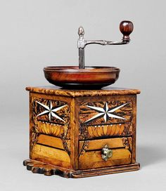 LAP COFFEE GRINDER _ France, early 19th c. Walnut, burlwood, fruitwood and ebony as well as bone inlaid with star and architectural motifs. Rectangular body with bowl-shaped hopper, iron crank and wooden handle. Drawer for the grinds. H 25 cm.