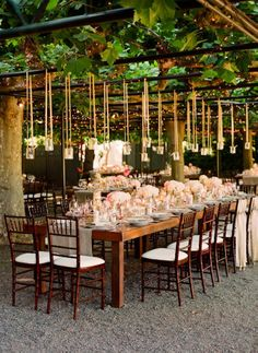 ribbon hung candles in jars over this pretty tablescape love the chair decor for two only chairs, with ribbons tied so cute. lovely bouquet on table and love a bare wooden table top with a runner. fairy lights through the overhead greenery.