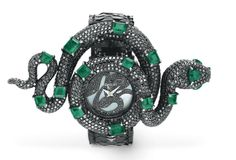 """AN EMERALD AND BLACK DIAMOND """"COBRA"""" WRISTWATCH, BY TREASURY  With quartz movement, the green circular dial with an applied circular-cut black diamond snake, within a circular-cut black diamond cobra surround, with variously-shaped emerald spots and face, to the snakeskin bracelet, mounted in silver, size adjustable Signed Treasury, Swiss"""