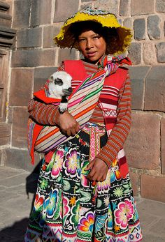 Harv Greenberg Photography - Cusco, Peru.  In Cusco, Peru, a young girl wears a jobona, a Quechua word for a traditional wool jacket. Indigenous Quechua women appreciate vibrant patterns and colorful buttons, which these jackets often bear. The traditional dress worn by Quechua women today is a mixture of styles from Pre-Spanish days and from Spanish Colonial peasant dresses.
