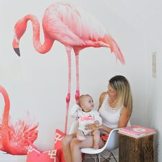Large pink vinyl flamingo on white wall featuring a standing position. In front is a mom looking at her baby sitting on a white chair beside a wooden book table.