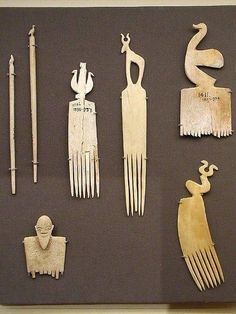 Predynastic Egyptian ivory hair combs and hair pins from the Naqada culture. Handles are decorated with symbolic motifs.