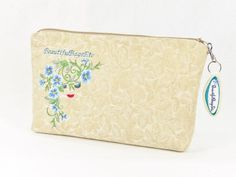 Lovely sky blue morning glory embroidery adorn this super cute zipper pouch. Upholstery weight fabric of tone on tone leaves in shades of ivory offer an attract