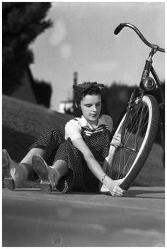 Judy Garland, the 13 year old MGM starlet, includes this in her play activities, as she examines her bicycle tire for proper condition