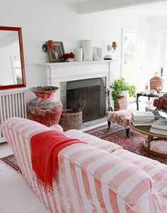 a red blanket draped over a striped sofa in front of a fireplace