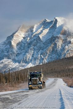 Semi tractor trailer travels the James Dalton Highway (the haul road) with mt Sukakpak rising in the distance.
