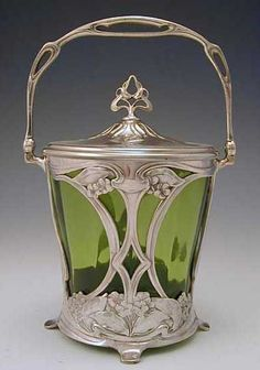 DescriptionSilver-plate on pewter & green glass biscuit barrel with art nouveau floral decoration Country of ManufactureGermany Datec.1906