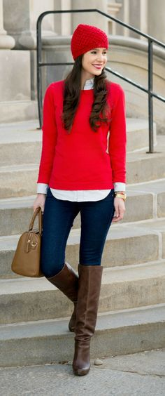 Cute and preppy casual outfit for winter! Red crewneck sweater over a classic blue and white striped Oxford with dark wash jeans, tall brown boots, a red knit beanie, and gold accessories.