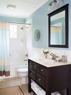 Watery-blue walls add color to the bathroom and give the space a calming spa-like feel. White tiles around the shower and white wainscoting keep the look fresh, while dark wood accents tie in the tile floor and rug. The mixture of blues, tans, whites, and wood makes the bathroom feel like a day at the beach.