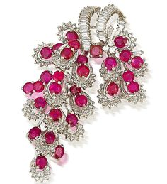 A ruby and diamond brooch  Formed as a highly articulated stylised bunch of grapes, set throughout with mixed-cut rubies, baguette and single-cut diamonds, mounted in 18k white gold