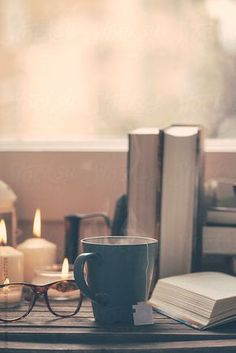 Still life of used books, tea, glasses and candles on a wood table. by BONNINSTUDIO   Stocksy United