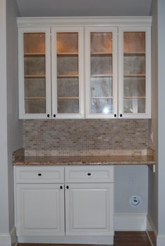 Custom designed and built cabinets, granite countertop, travertine tile backsplash, glass-front wall cabinets and space for under-counter wine fridge
