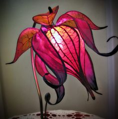 Bring a bit of magic to your home, and gently light the night with this hand made silk flower lamp. The flower is hand dyed and painted and mounted on an art nouveau style lily pad base.  A 15 watt magenta bulb creates a soft glow. The lamp plugs in with a standard two pronged plug designed for North American outlets and a spare bulb is included with purchase.