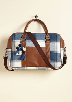 A reliable way to haul travel essentials is a must-have for every jet setter, and this plaid weekend bag is just the piece for the job! Blue, cream, and taupe hues along with faux-leather accents detail the exterior of this carry-all, while its roomy interior seals its steadfast appeal.