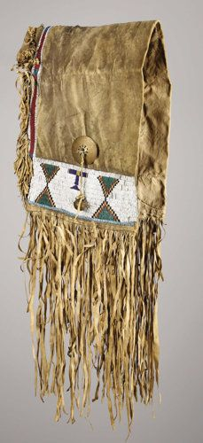 c. 1880  sinew sewn and lane-stitched in classic shades of glass seed beads, each side decorated with pairs of stepped triangles, trimmed with brass brooches, brass bells and long hide fringe  Length: 42 inches excluding fringe Cheyenne saddle bag  1880