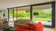Woonkamer met extra grote houten schuifpui geeft maximaal uitzicht op de grote groene tuin rondom de villa. Windows, Living Room, Room