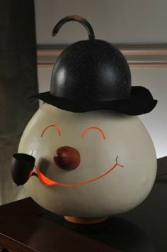 Our new snowman head is white in color witha black top. He has an orange carrot gourd nose and a gourd pipe. Approximately 8 inches in diameter and comes with an electric light.
