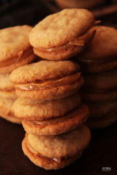 Beijo de Dama - 200g de amendoim torrado e sem a pele (ou 200g de amêndoas sem pele) - 200g de farinha de trigo - 200g de manteiga sem sal em temperatura ambiente - 200g de açúcar - 100g de doce de leite pastoso (ou 75g de chocolate meio-amargo e 50g de creme de leite) para o recheio